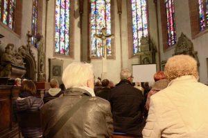 Publikum, im Hintergrund Kreuz